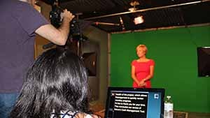 A woman being filmed against in a  green screen studio.