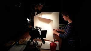 An artist drawing on a lighted whiteboard.